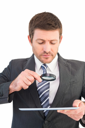 Businessman looking at tablet with magnifying glass on white background photo