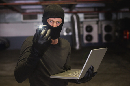 shadowy: Hacker using laptop to steal identity on shadowy background Stock Photo