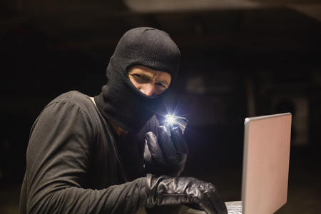 to steal: Hacker using laptop to steal identity on shadowy background Stock Photo
