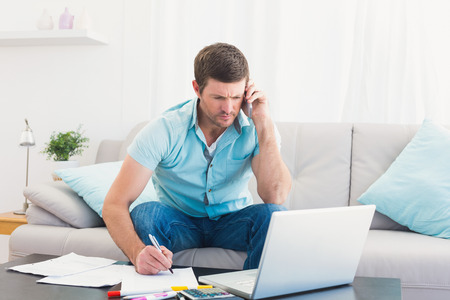 call out: Serious man with a phone paying his bills on laptop at home in the living room