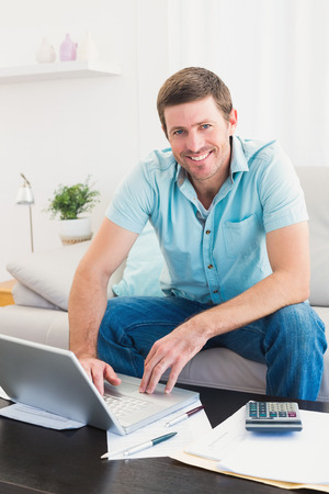 figuring: Smiling man on a laptop sitting on a sofa at home paying his bills