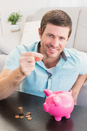 pennie: A man showing a pennie with a piggy bank on the coffee table