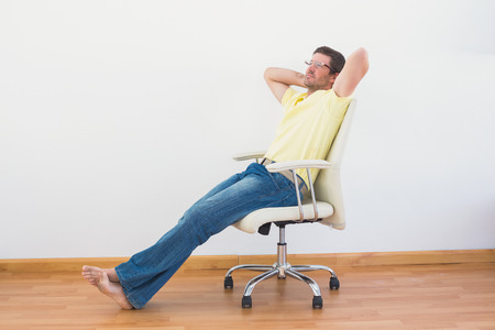 a man leaning back in swivel chair at home in the living room stock photo