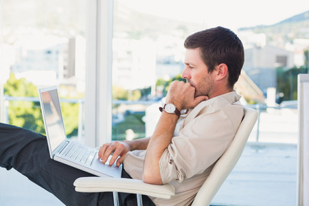 relaxed: Relaxed businessman with a laptop in his office