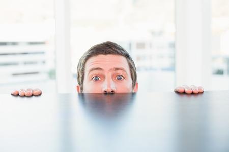 Nervous businessman peeking over desk in his office Stock Photo - 33953055