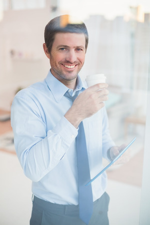 Smiling businessman holding tablet and disposable cup looking out the window in his office photo