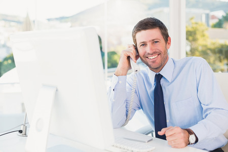 computer monitors: Smiling businessman phoning at his desk in his office