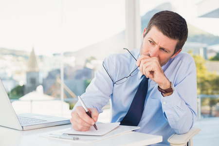 worried businessman: Worried businessman writing on is notepad in his office Stock Photo