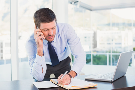 mobile phone adult: Businessman writing and phoning at his desk in his office