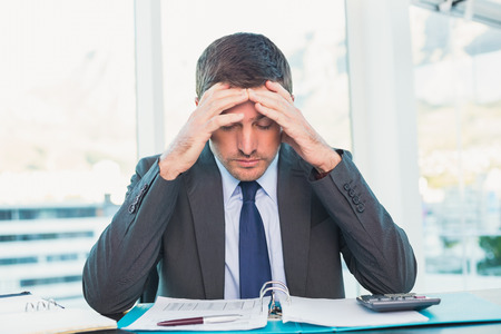 stressed: Stressed businessman with head in hands in his office