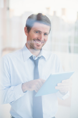 Smiling businessman using tablet looking out the window in his office photo
