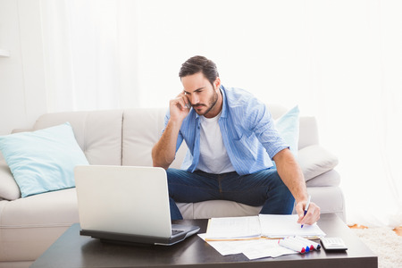 phone call: Man paying his bills with laptop while talking on phone in the living room