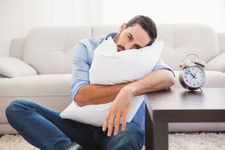 tired: Exhausted man sleeping with head resting on pillow in the living room
