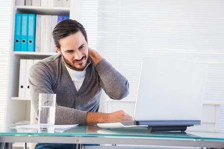 オフィスで首の痛みを持つハンサムな実業家の顔をしかめ 写真素材