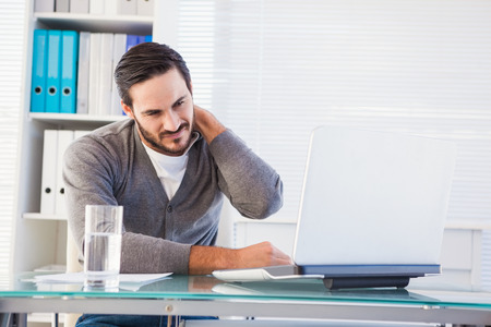 pain: Frowning handsome businessman having neck pain in the office