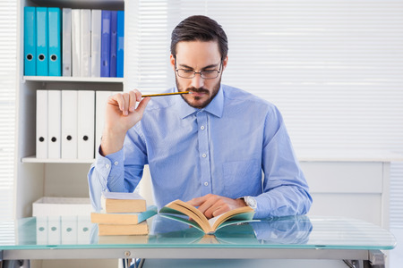 reading glasses: Focused businessman reading book at desk in the office
