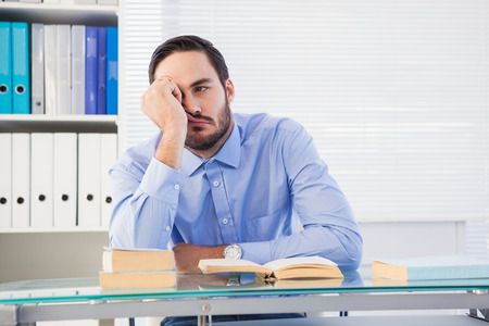 slumped: Casual bored businessman at his desk in the office