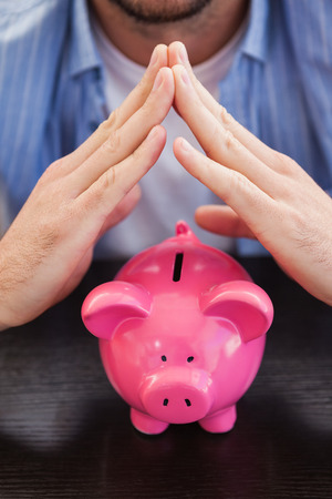 sheltering: Casual man sheltering piggy bank in the living room Stock Photo