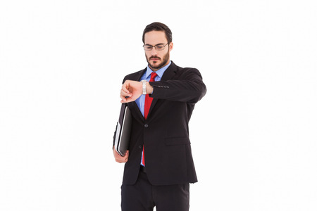 cut wrist: Frowning young businessman checking time on white background Stock Photo