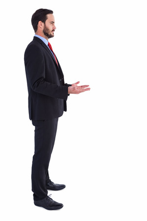 frowning: Frowning businessman presenting with hands on white background Stock Photo