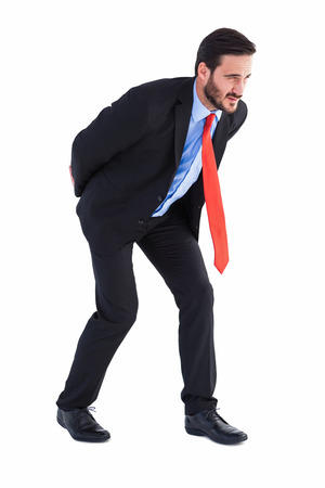 Businessman in suit carrying something heavy on white background Stock Photo