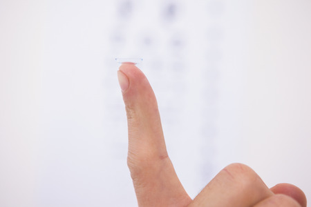 sense of sight: Close up on finger holding contact lens on white background