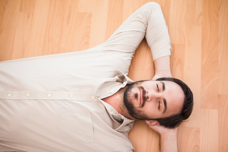 domicile: Young man lying on floor thinking in the living room