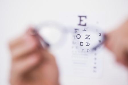 eye test: Reading glasses looking at eye test on white background Stock Photo