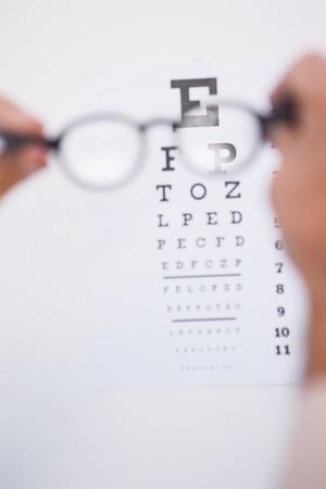 gafas de lectura: Gafas de lectura mirando examen de la vista en el fondo blanco