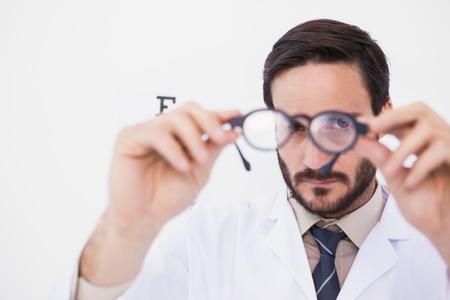 bata de laboratorio: M�dico con bata de laboratorio mirando a trav�s de gafas en el fondo blanco