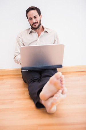 mid adult men: Relaxed businessman sitting on the floor while using laptop in the living room