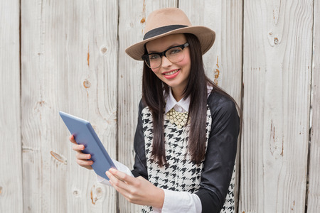Pretty hipster using tablet pc against bleached wooden planks photo