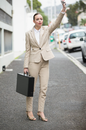 hailing: Young businesswoman hailing a cab outside in the city
