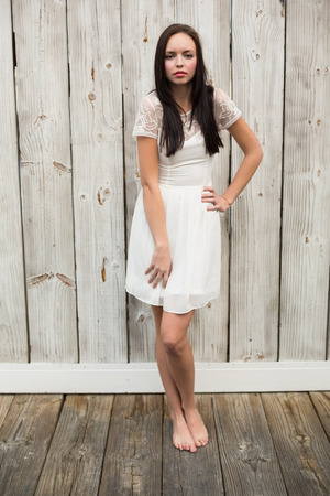 eclectic: Pretty brunette posing in white dress against bleached wooden planks