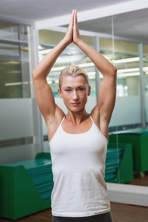 manos unidas: Retrato de una mujer joven deportiva con las manos juntas sobre la cabeza en el gimnasio