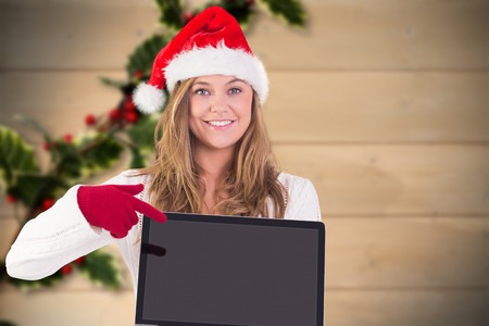 Festive blonde pointing to laptop against blurred holly on wood photo