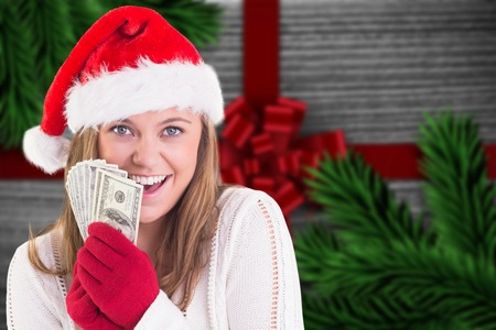 Festive blonde showing fan of dollars against festive bow over wood photo