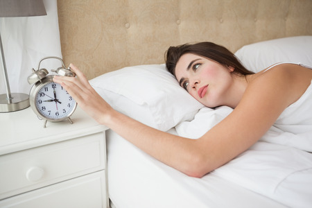 turning off: Pretty brunette turning off her alarm at home in the bedroom