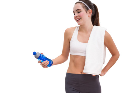 Fit brunette looking at sports bottle on white background photo