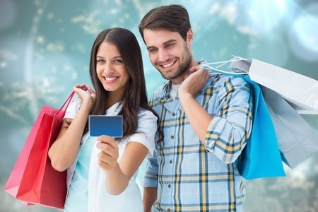 Couple with shopping bags and credit card against blurred christmas background photo