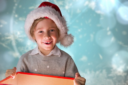 opening gift: Festive boy opening gift against blurred christmas background
