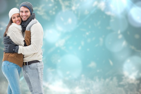 embracing couple: Young winter couple against blurred christmas background Stock Photo