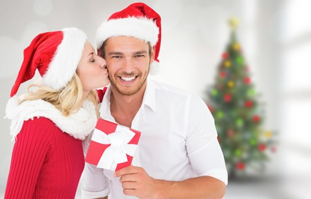 Young festive couple against blurry christmas tree in room photo