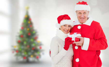 Festive mature couple holding gift against blurry christmas tree in room photo