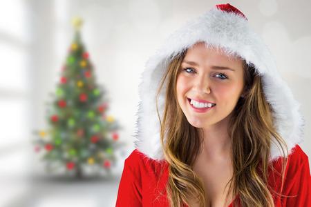 pere noel sexy: Sexy Santa Girl souriant � la cam�ra contre arbre de No�l floue dans la chambre