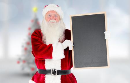 Santa claus showing blackboard against blurry christmas tree in room photo