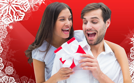 Woman surprising boyfriend with gift against christmas themed snow flake frame photo