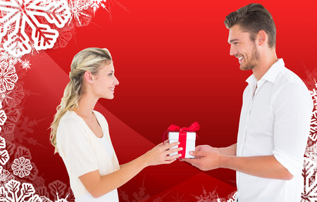 Young couple with gift against christmas themed snow flake frame photo