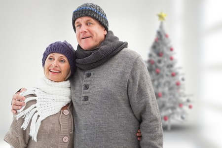 Mature winter couple against blurry christmas tree in room photo