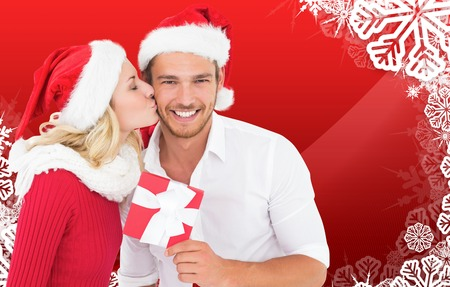 Young festive couple against christmas themed snow flake frame photo